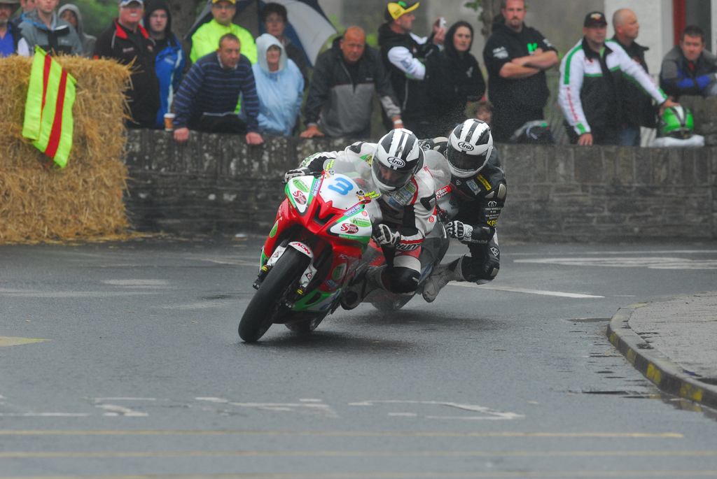 The crowd watch on as Michael Dunlop leads older brother William into Athea Village in a wet Supersport race in 2011